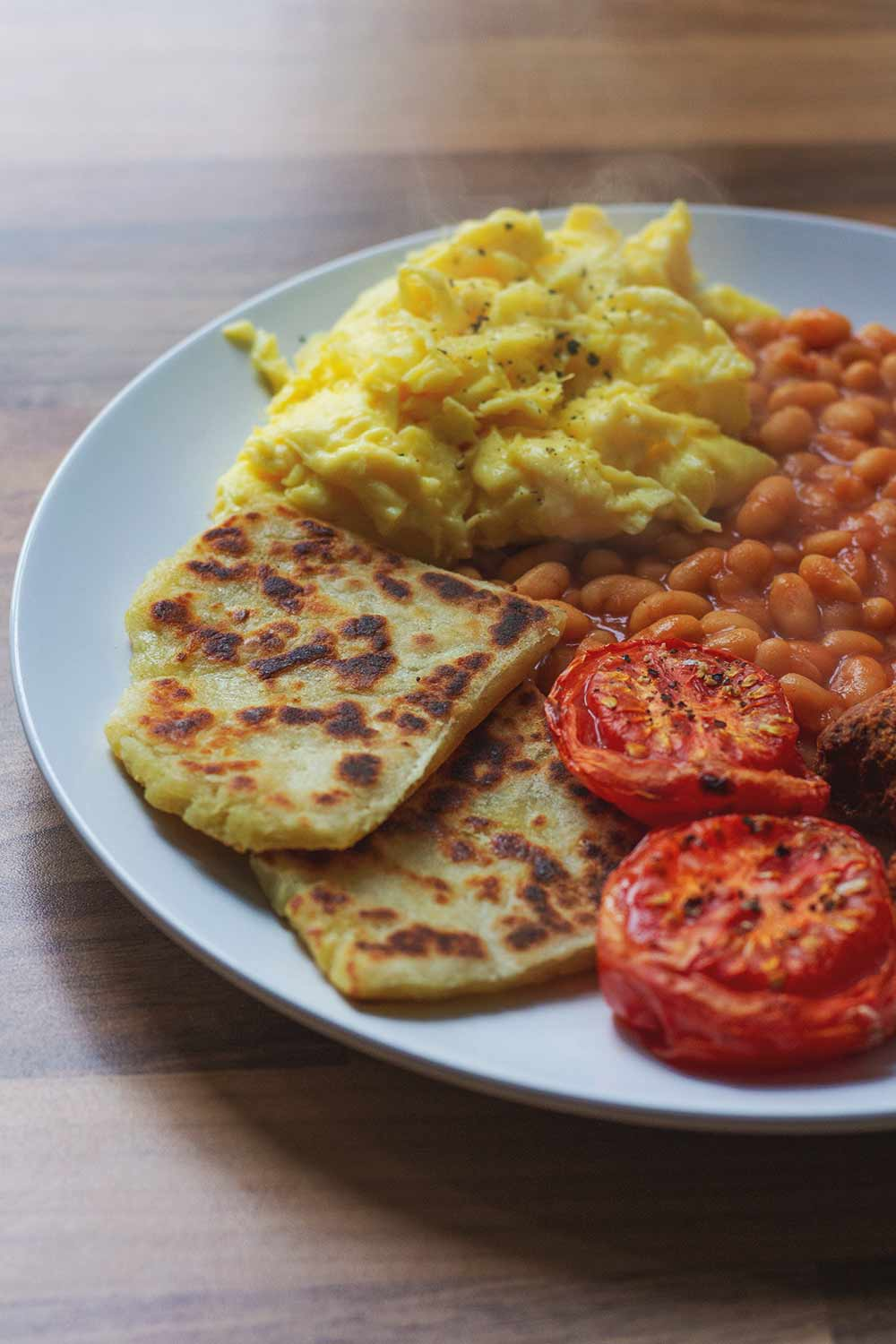 A Scottish breakfast of potato scone, scrambled eggs, tomato, baked beans and vegetarian sausage
