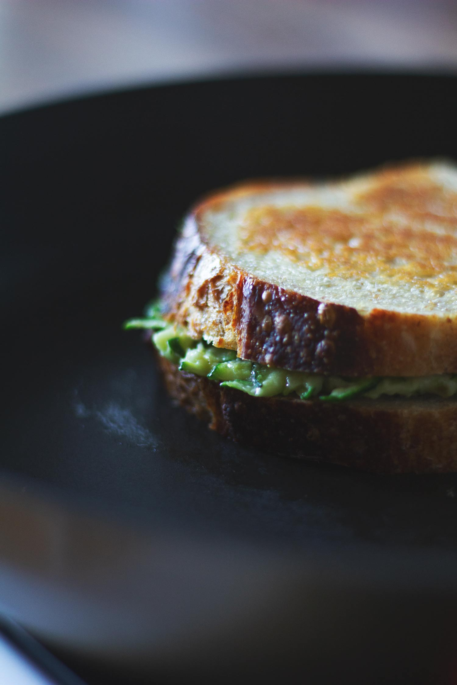 Courgette grilled cheese being toasted in a frying pan