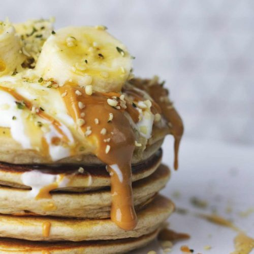 A stack of pancakes with peanut butter dripping down
