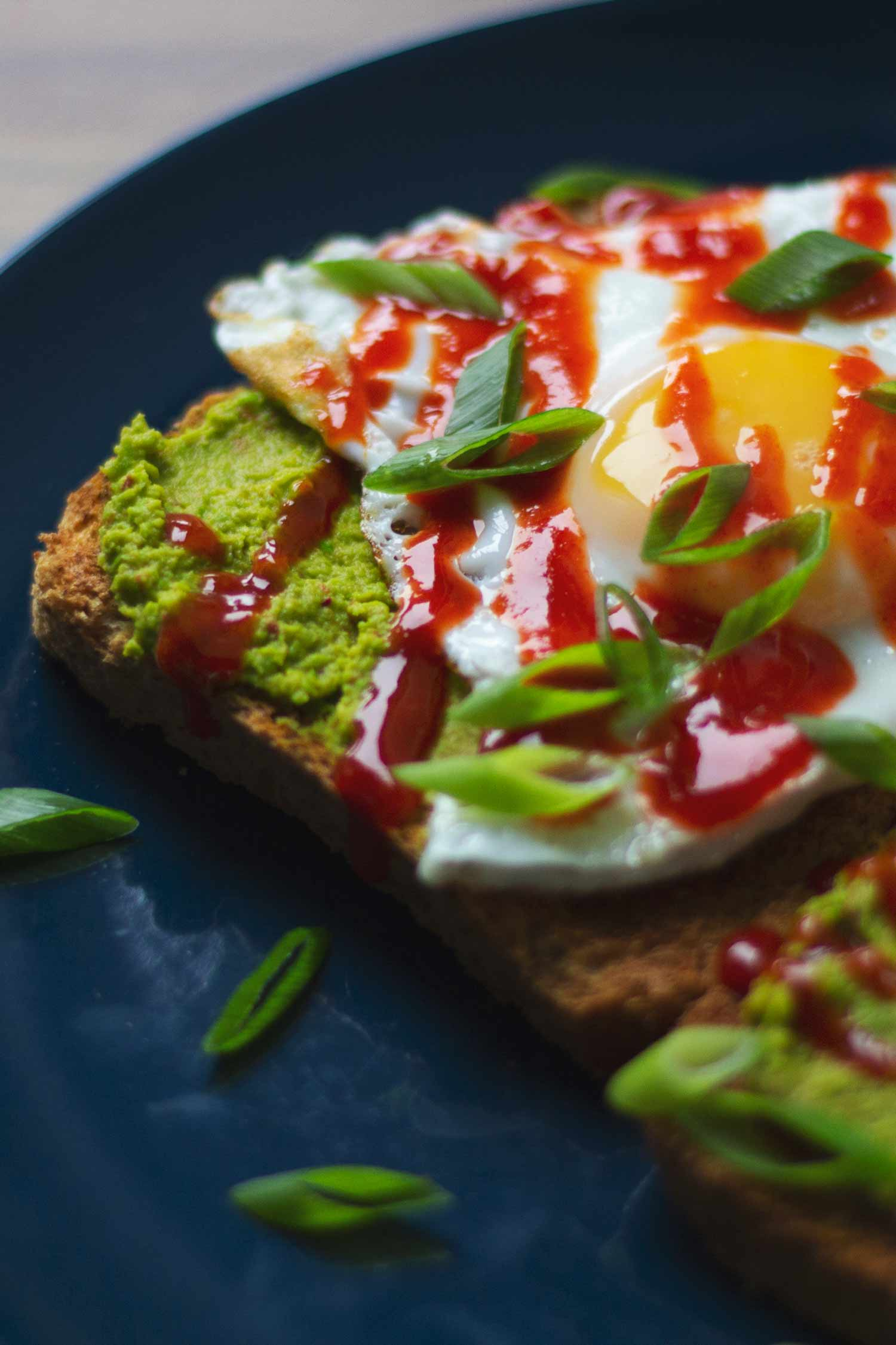 Toast topped with pea and chilli puree, fried egg and sriracha