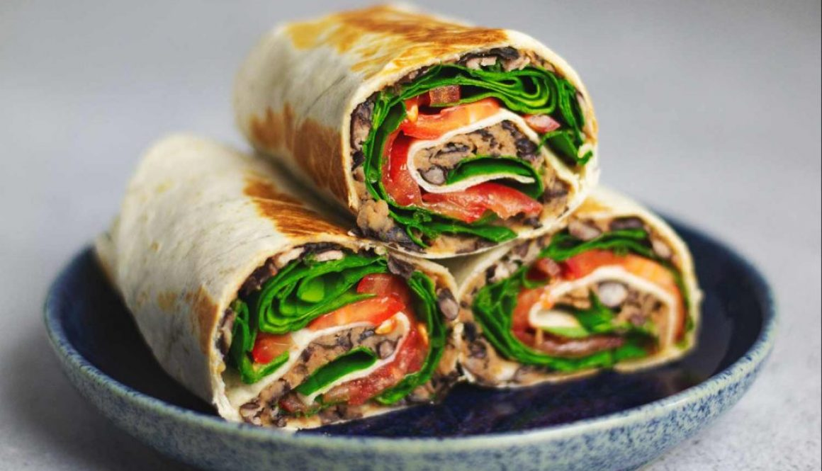 A tortilla wrap filled with black beans, cheese, spinach and tomato