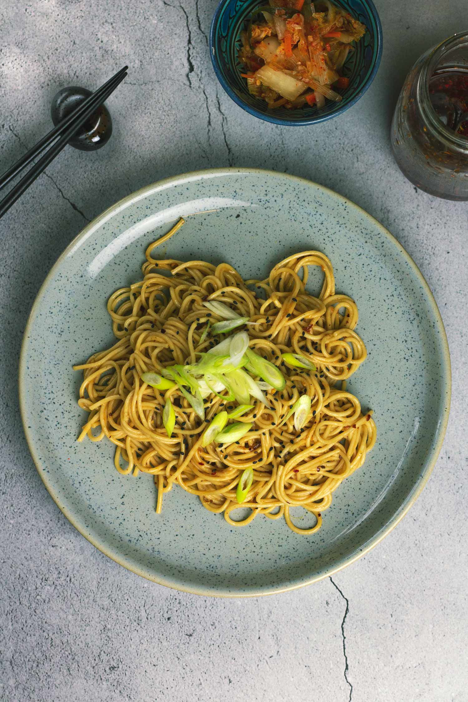 A plate of noodles topped with spring onion