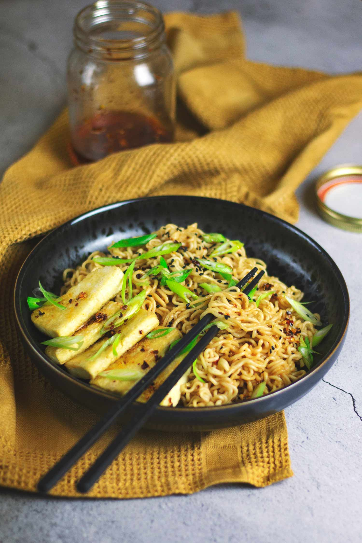 A bowl of peanut chilli noodles and tofu with chopsticks