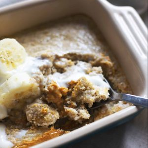 A close up of a spoon in a dish of baked oats