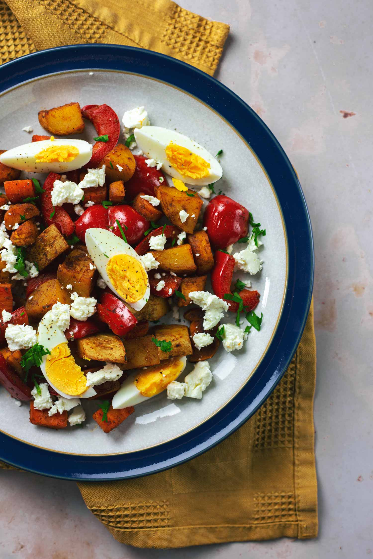 A plate of vegetables topped with chopped boiled egg and feta cheese