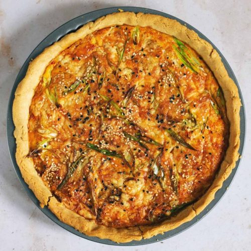 A close up of a quiche with sesame seeds on top