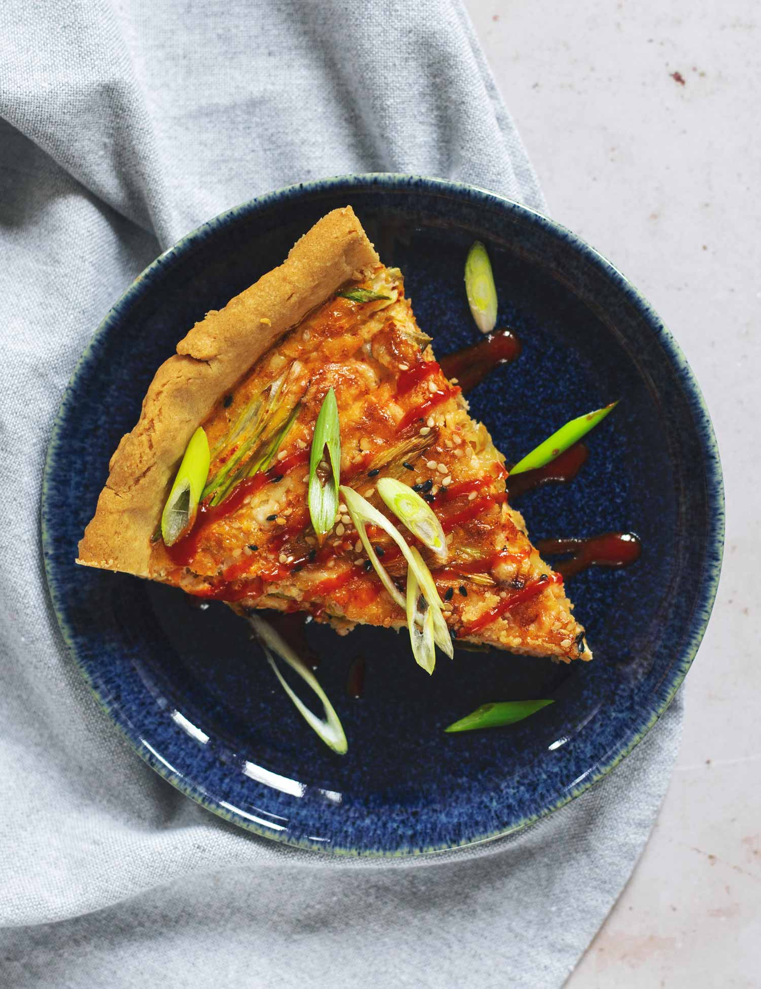 A slice of quiche with spring onion and red hot sauce on top