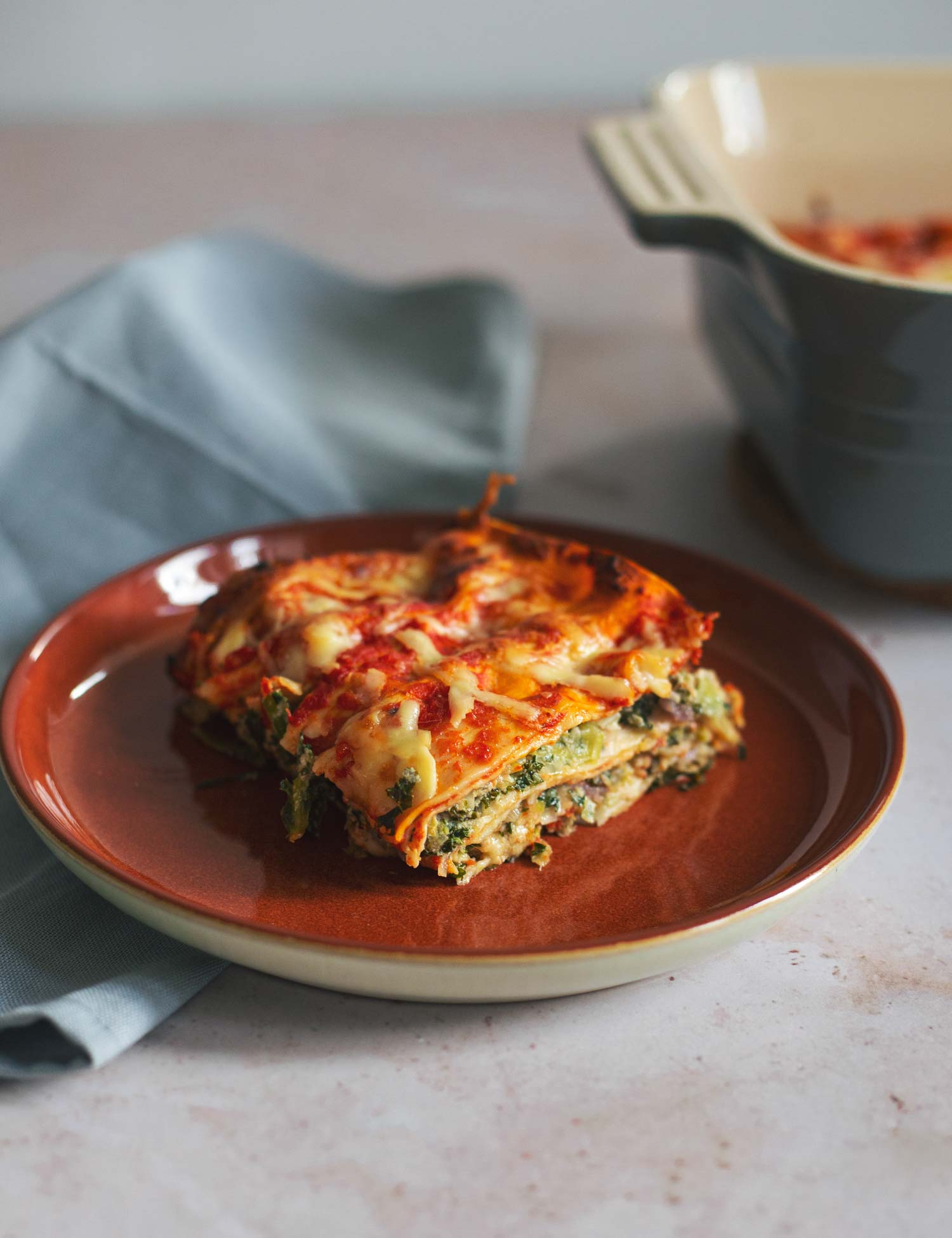 A slice of lasagne with a baking dish with more lasagne in the background