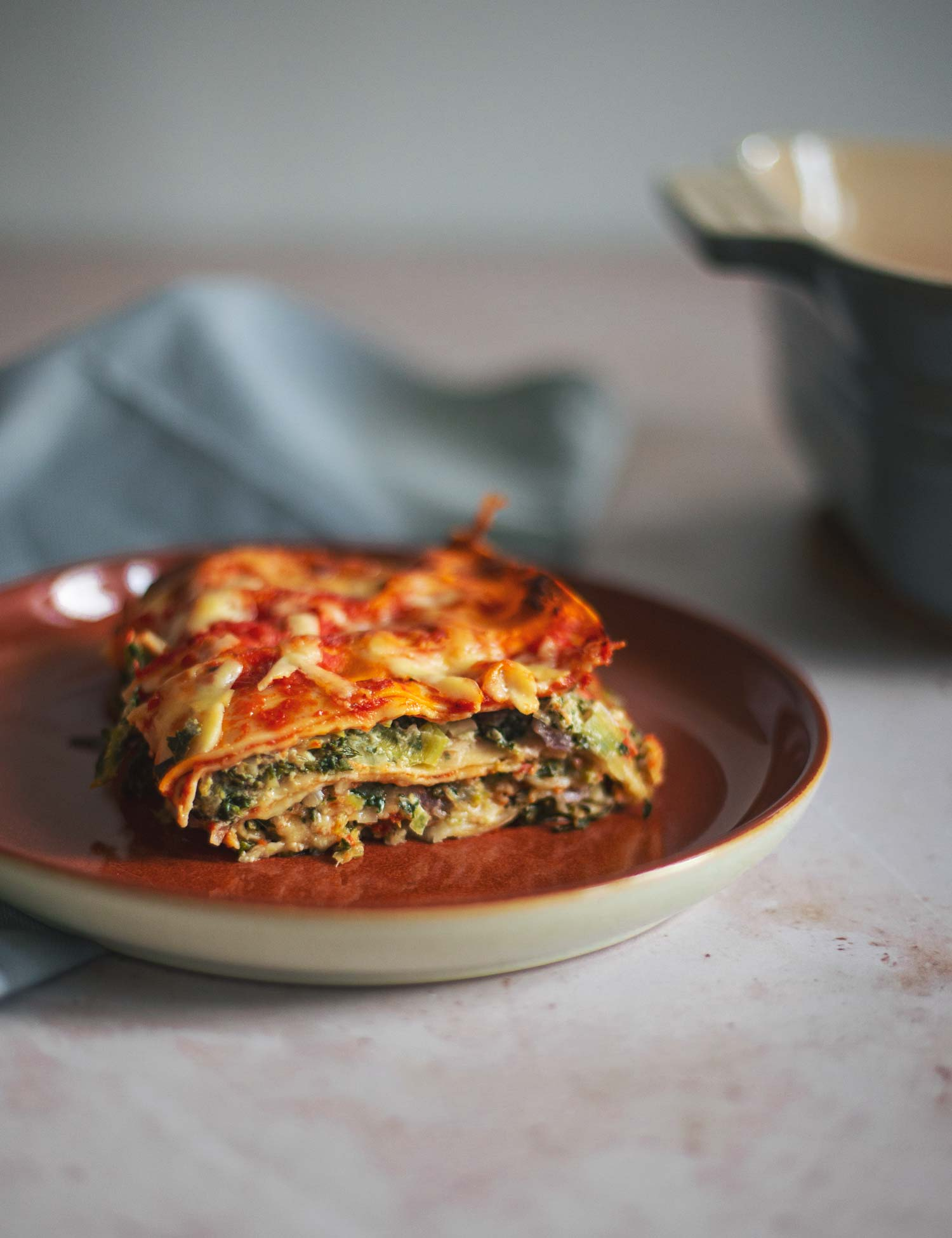 A slice of lasagne on a red plate with a casserole dish in the background