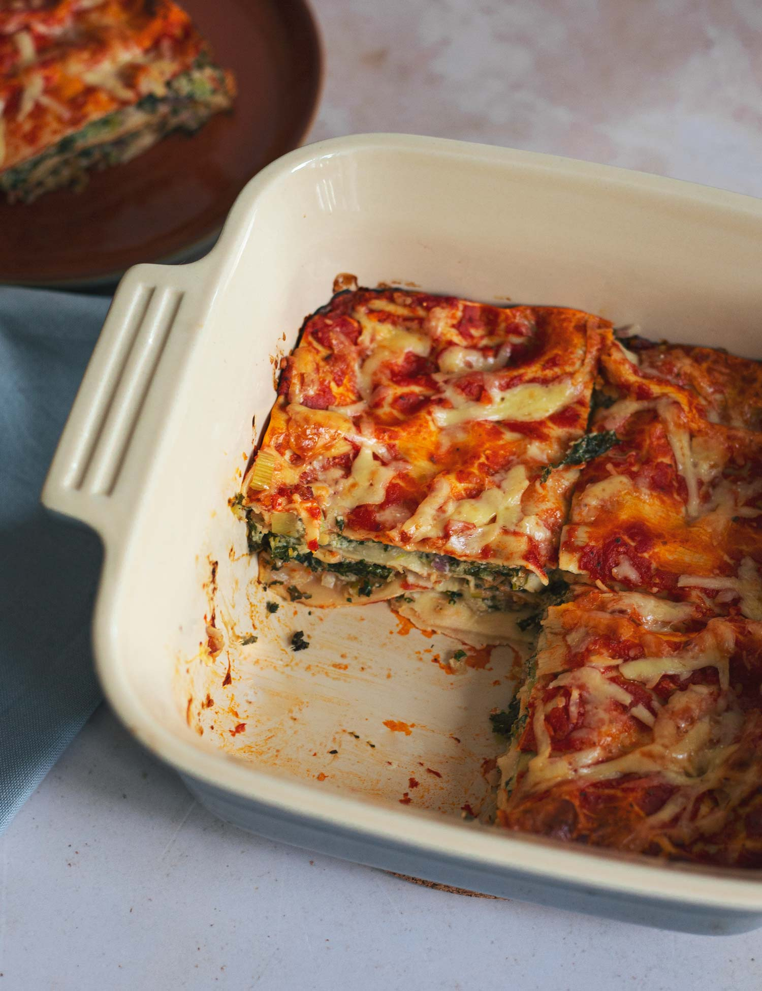 An oven dish with three slices of vegetable lasagne in it