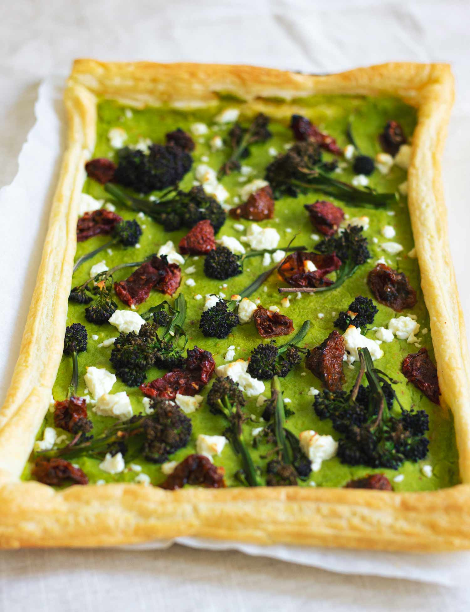 A tray with a rectangular tart topped with pea puree, broccoli, feta and sundried tomato
