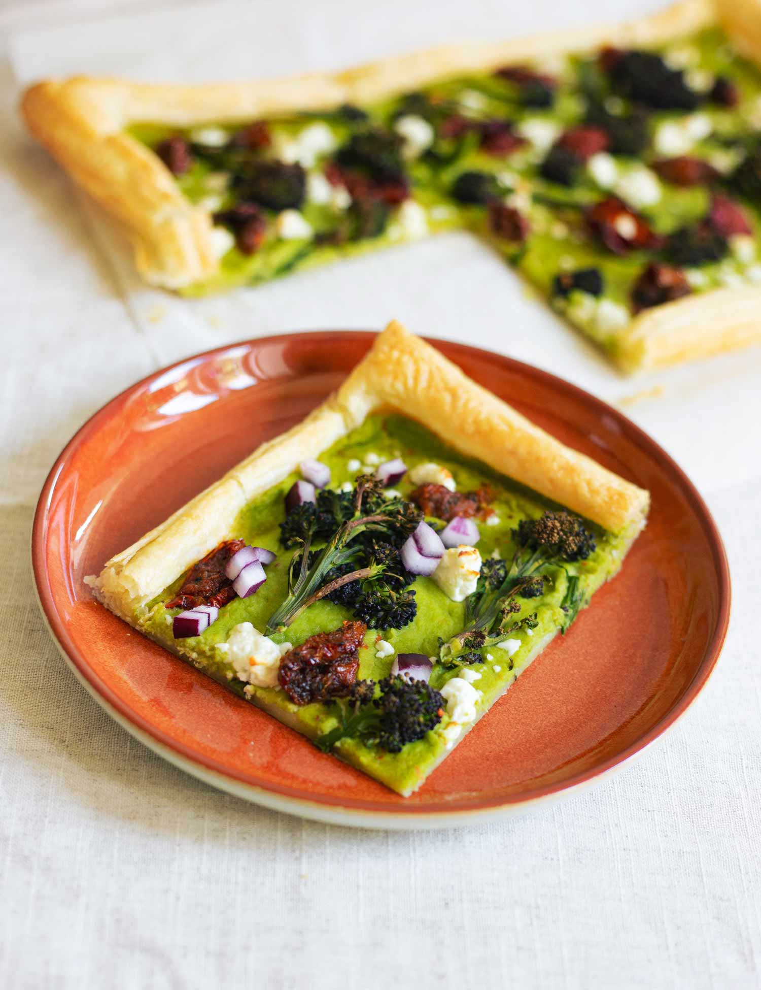 A slice of a pastry with a green puree, broccoli, tomato and cheese on top