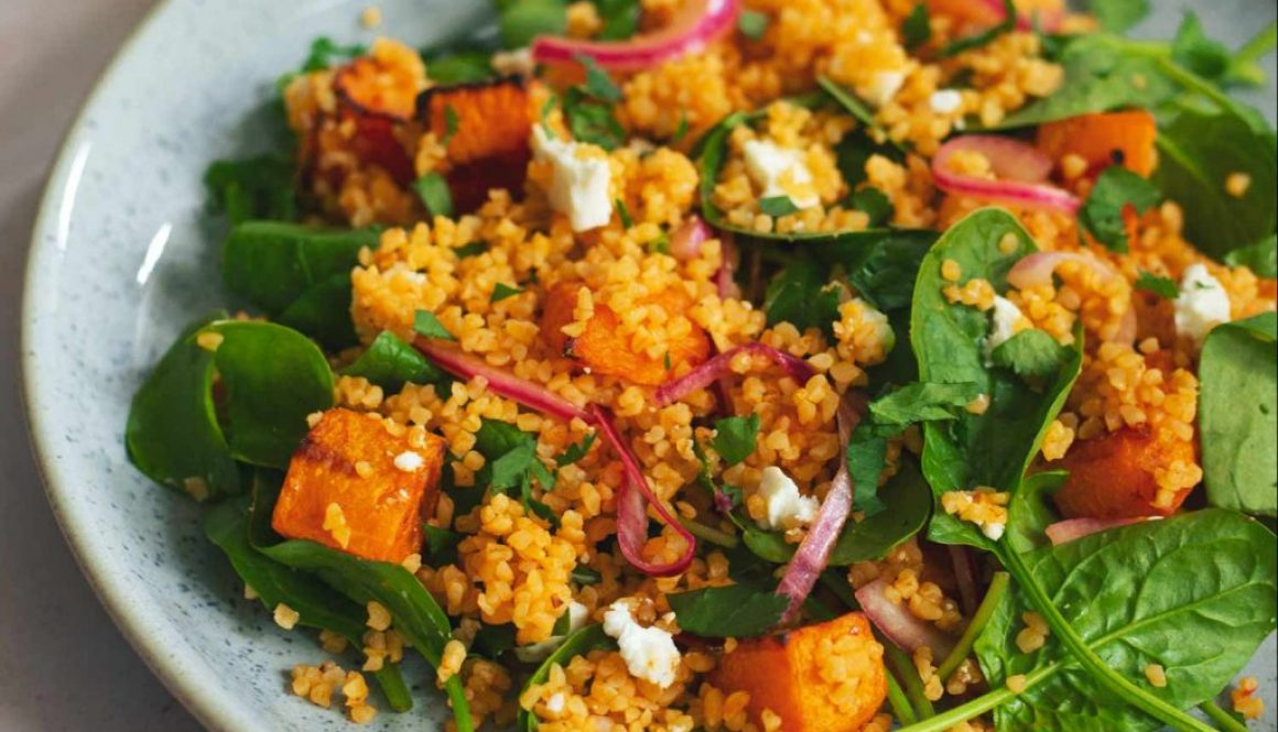 A colourful salad with squash, spinach, bulgur wheat and feta