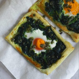 Two pastry tarts with greens and egg on baking parchment