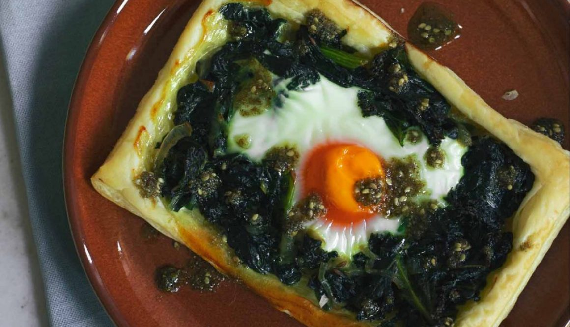 A pastry tart with greens and eggs on a red plate