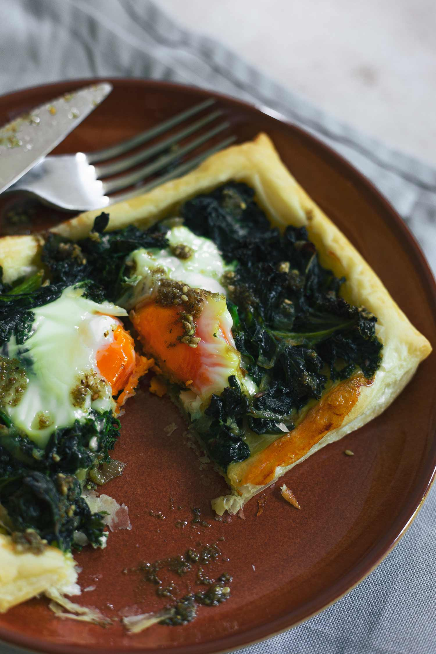 A pastry tart with greens and eggs cut in half
